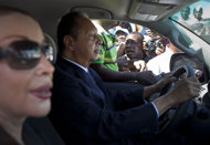 "FILE - In this Friday Jan. 20, 2012 file photo. former dictator Jean-Claude ""Baby Doc"" Duvalier drives away from the courthouse with longtime companion Veronique Roy, after attending a closed hearing in Port-au-Prince, Haiti. A Haitian judge said Monday Jan. 30, 2012, that Duvalier should face trial for corruption, but not the more serious charges of human rights violations committed during his rule. Jean said the statute of limitations had run out on the human rights charges but not on the accusations of misappropriation of public funds. (AP Photo/Ramon Espinosa, File)"